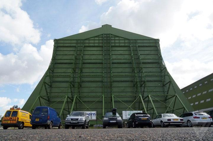 Rumah pesawat hibrid terbesar sejagat di pabrik pesawat bersejarah di Cardington Airfield, Bedfordshire, Inggris. Airlander berada di balik pintu hijau zamrud Hangar 1, yang menjadi milik HAV. Di tempat itu, ada pula hangar mili Warner Bros Pictures. Perusahaan pembuatan film itu juga memiliki hangar yang menjadi tempat di mana film Peter Pan baru yang dibintangi Hugh Jackman diambil. Tidak mau kalah dengan skala usaha tetangga mereka, produsen WB rupanya membangun sebuah kapal bajak laut skala penuh untuk film ini. (Foto: The Verge)