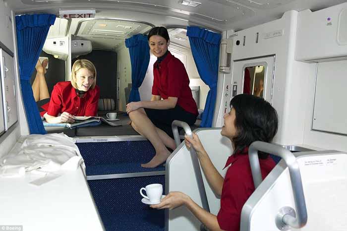 Staf mengobrol dan bersantai dengan majalah dan minuman di dalam ruang istirahat kru pada Boeing 777